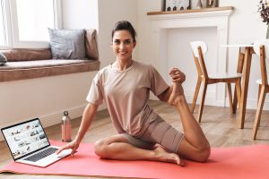 woman taking an online yoga class to practice self-care during the covid-19 crisis. She also gets online therapy in florida for anxiety with counseling solutions of broward