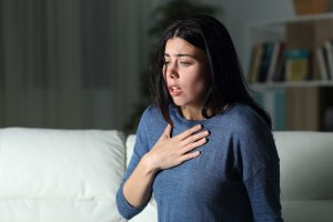 latina with her hand over her heart having a panic attack. She gets help for her anxiety with anxiety treatment in miramar florida at Counseling Solutions of Broward 33023