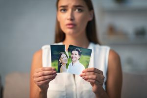 sad woman coping with divorce holds up a photo of herself and her ex at their wedding. She gets help after a breakup in counseling for divorce recovery in Florida with Counseling Solutions of Broward. post-divorce counseling in florida can help you heal and move forward.