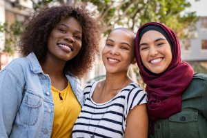 multiethnic women looking at the camera smiling. The woman in the middle received codependency recovery counseling in miramar, florida and online therapy in florida for depression with counseling solutions of broward