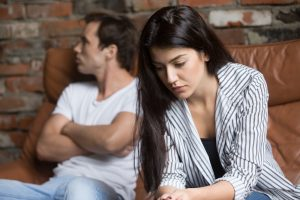 unhappy couple sits on their couch. The woman gets help from therapist Enid De Jesus during individual relationship counseling in Miramar, FL at counseling solutions of broward. interpersonal relationship counseling in florida can help you have a better life.