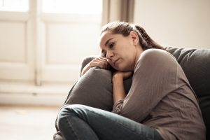 woman sitting on the couch with depression. She gets depression treatment for women in Florida at counseling solutions of broward with therapist Enid De Jesus in Miramar, FL