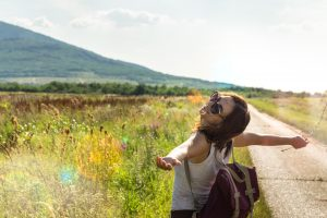 Beautiful Woman Smiling In Nature with arms out looking up at the sun. Begin counseling for self confidence miramar, FL with broward counselor, Enid, or in online therapy for women in Florida