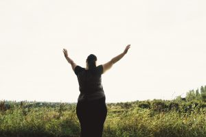 Woman raising hands up, looking confident and happy in a field. Body Positive, Freedom, High Self Esteem, Confidence, Happiness and Finding Fulfillment in Florida with Broward counselor Enid De Jesus for online therapy in Florida.