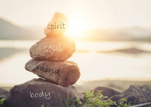 """Stacked rocks outdoors with """"spirit. soul. mind. body."""" labeled on them. Find Fulfillment with online therapy for women in Florida with Broward counselor Enid De Jesus."""