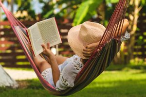 Woman Relaxing In Hammock. Beautiful Woman Reading Book in a hammock in Miramar, FL. She is having sleep problems and suffering from insomnia and a lack of sleep. Get sleep hygiene tips in Florida from Counseling solutions of Broward.