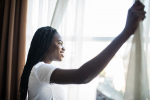 Morning Of Beautiful Young Woman Opening Curtains In Bedroom In Miramar, FL. She is having sleep problems and suffering from insomnia and a lack of sleep. Get sleep hygiene tips in Florida from Counseling solutions of Broward.