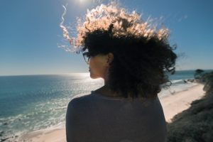 Woman looking at the beach in the sunshine considering anxiety treatment with online therapist, Enid, for online therapy in Florida. You can get help with imposter syndrome, codependency treatment and perfectionism counseling for women in miramar, fl.
