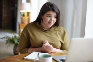 Woman holding her hands together and looking at her computer screen talking to try anxiety treatment with online therapist, Enid, for online therapy in Florida. You can get help with imposter syndrome, codependency treatment and perfectionism counseling for women in miramar, fl.
