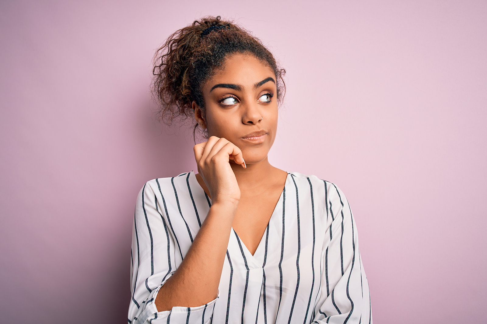 Young beautiful african american woman wearing striped t-shirt on a pink background looking like she has some questions about online therapy in Florida. You can find anxiety treatment with online therapist, Enid, for online therapy in Florida. You can get help with imposter syndrome, codependency treatment and perfectionism counseling for women in miramar, fl.
