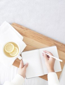Woman's hand writing in a notebook with a cup and a couple of other notebooks on a white table. She is enjoying the benefits of journaling for high-performing women for confidence building in Miramar, FL. She gets online therapy in Florida for women with anxiety and codependency and perfectionism.