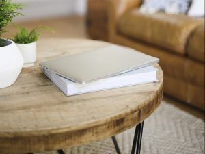 Journal on a table with two plants and a sofa in the background. Learn more about the benefits of journaling for high-performing women for confidence building in Miramar, FL. She gets online therapy in Florida for women with anxiety and codependency and perfectionism.