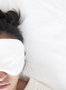 Woman wearing a face mask laying in bed after post-divorce counseling in florida. You can get online therapy in Florida for anxiety treatment in Miramar, codependency therapy, counseling for self-sabotage, imposter syndrome for high-achieving women, divorce recovery and more with online counseling for women with anxiety in Miramar, FL. Meet with online therapist in Florida, Enid.