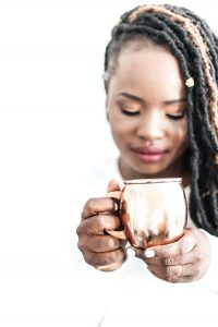 Woman looking at a mug in her hand, finding fulfillment in Florida with anxiety treatment for women in florida. You can get online therapy in Florida for codependency, self-sabotage, imposter syndrome, divorce recovery and more with online counseling for women with anxiety in Miramar, FL. Meet with online therapist in Florida, Enid.