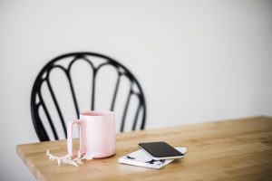 Chair at table with coffee cup, flower sprig, phone and notebook for a morning routine for healthy boundaries in Miramar, FL. You can get codependency therapy in Miramar, FL with Florida online therapist for women with anxiety, Enid.
