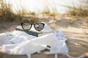 Sunglasses on top of a book on a blanket on the beach in Miramar, FL. You can get codependency counseling for women in Florida with online therapist Enid to talk about setting healthy boundaries in Miramar, FL