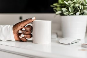 Hand holding a coffee cup on a white table with a plant. You can get codependency counseling for women in Florida with online therapist Enid to talk about setting healthy boundaries in Miramar, FL