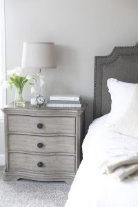 Photo of a bed with grey headboard and grey side table with flowers and books belonging to a woman experiencing dating anxiety in Miramar, FL. You can get online therapy in Florida for codependency and setting boundaries in MIramar, FL from an online therapist who specializes in relationship counseling for singles.