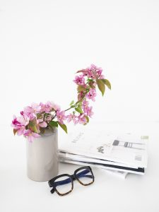 Pink flowers in a marbled vase with magazines and a pair of glasses on a white table. You can get online therapy in Florida for codependency and setting boundaries in MIramar, FL from an online therapist who specializes in relationship counseling for singles.