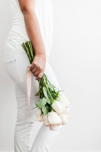 Person wearing all white, holding white roses. You can get online therapy in Florida for codependency and setting boundaries in MIramar, FL from an online therapist.