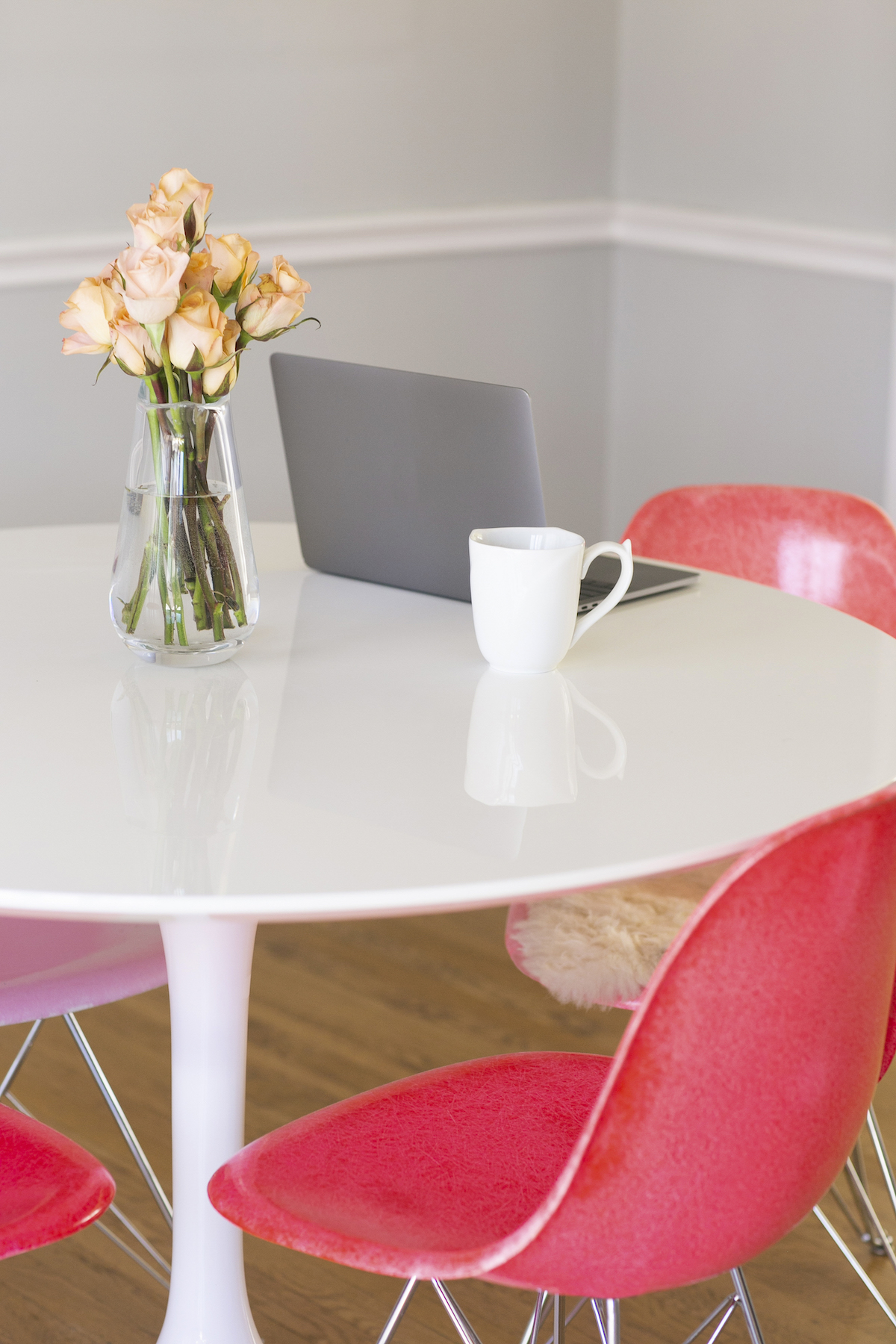 White table with pink chairs around, with laptop, flowers and coffee cup on the table. A Miramar, FL therapist for women gives tips for a self-compassion practice with perfectionism counseling in Miramar, FL. You can get online therapy in Florida here.