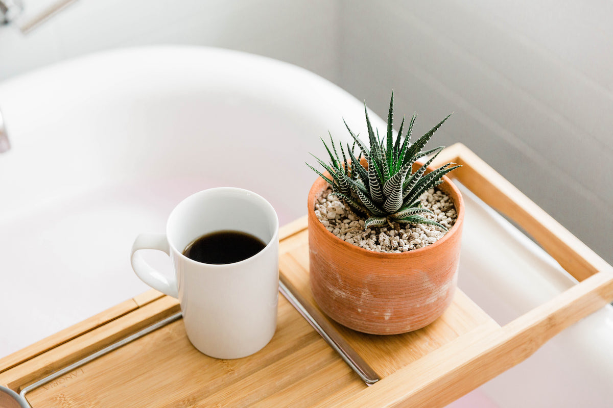 Coffee cup and plant on a wooden tray over the tub. You can practice self care with healthy boundary management for codependency treatment, anxiety treatment, divorce recovery in Miramar, FL and more with online therapy for women in Florida.