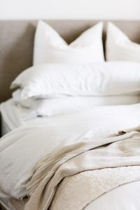 Bed with white linens and pillows. Women in Florida can get codependency treatment for developing healthy sexual boundaries in Miramar, FL and with online therapy in Florida