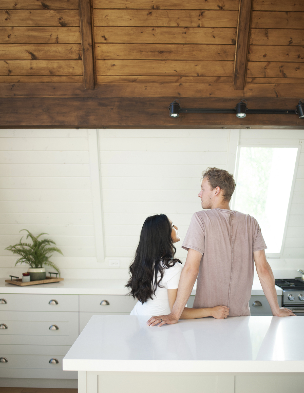 Couple standing against island in kitchen looking at each other with arms around each other. Talking about healthy sexual boundaries can be hard. Getting therapy for codependency in Miramar, FL can help with online therapy in Florida