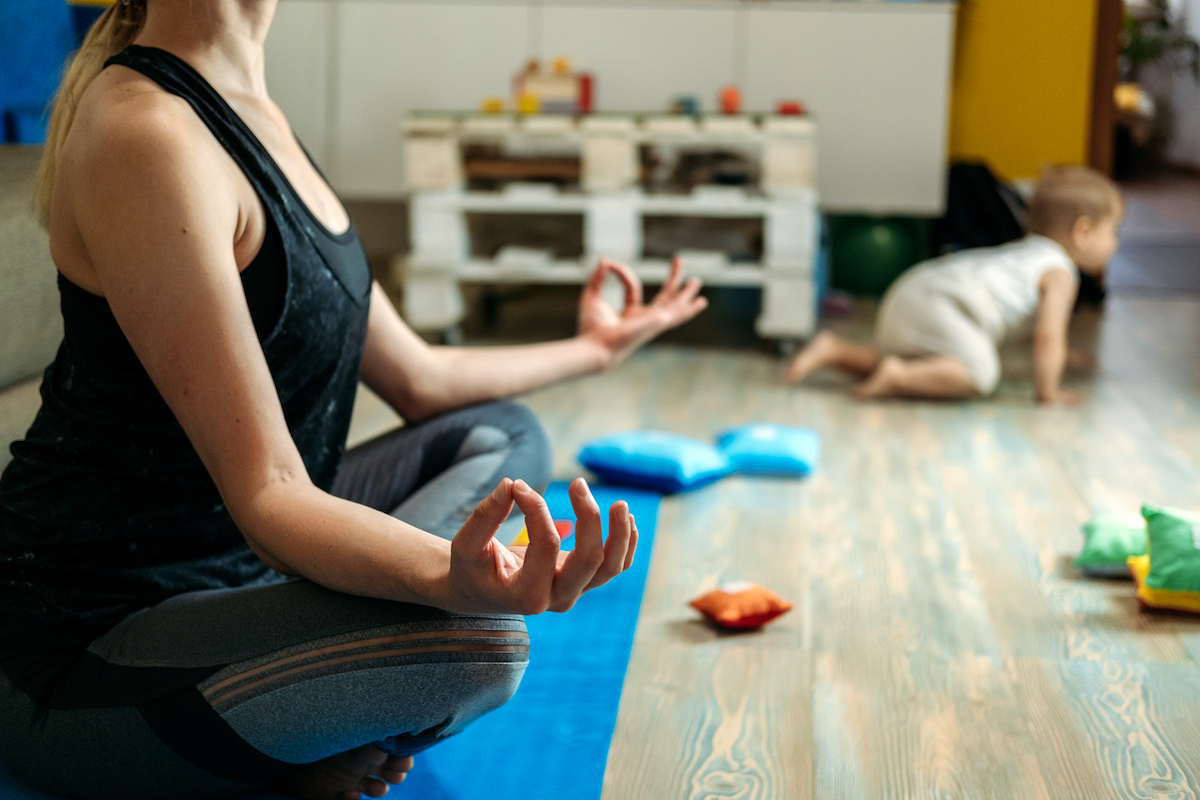 Mindfulness meditation concept. Young woman, mother practicing yoga at home sitting in lotus pose, meditating relaxing with closed eyes with baby daughter at home. Support for women in Miramar, FL is here with Broward counselor, Enid. You can get help with online therapy for women in Florida here!