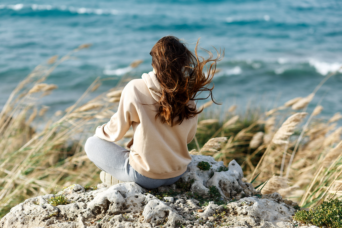 Young yoga woman meditation, mindfulness on seaside rock cliff edge. Finding yourself after codependency therapy with a broward counselor can help if you find yourself young and divorced. Divorce recovery can provide support for women in Miramar, FL and beyond.
