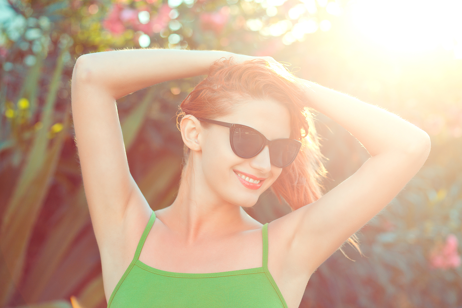 Closeup Portrait Happy Young Business Woman In Sunglasses and Green shirt in the sun. She feels free, just like women in miramar, FL can feel after doing anxiety treatment with a skilled online therapist in Florida here.
