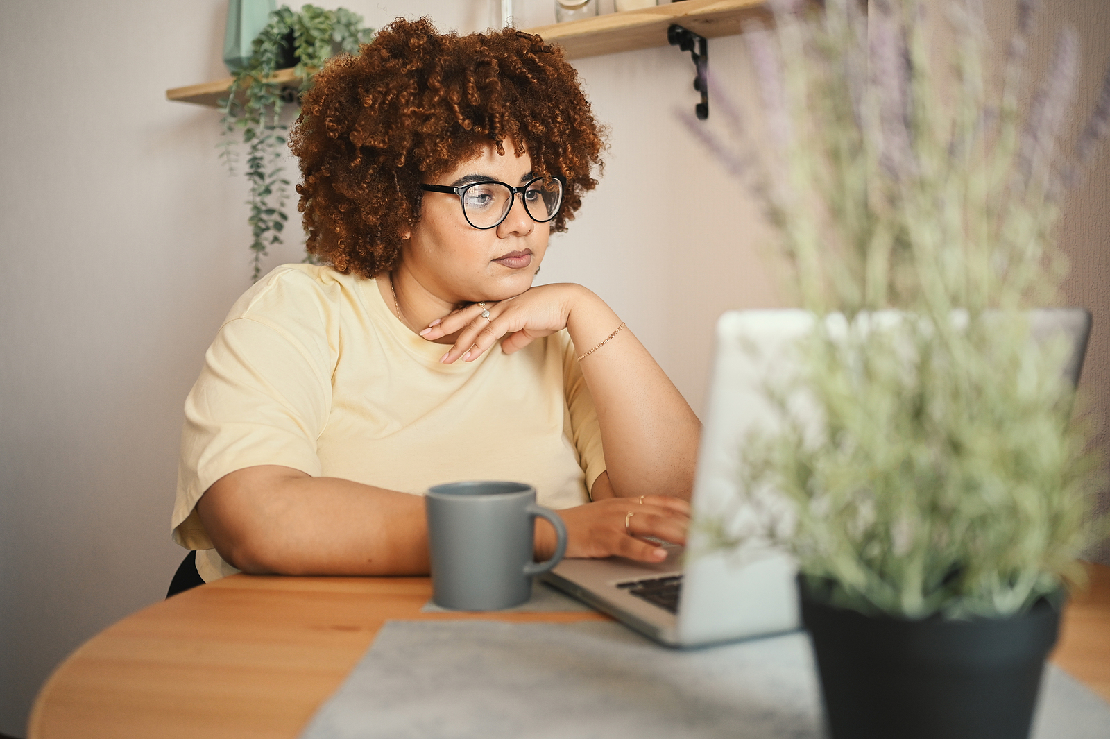 Woman on laptop with plants around her and a cup of coffee or tea. Find codependency treatment in Miramar, FL for healthy boundaries with online therapy in Florida.